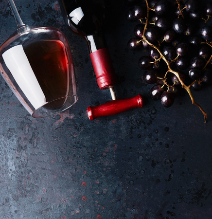 Red wine concept.  Glass with red wine,  bottle and red grape clusters on black rustic background, top view. Place for your design, text, article, advertisement or product.