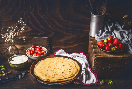 Homemade crepes on dark rustic kitchen table with strawberries and yogurt in bowls . Country style food still life