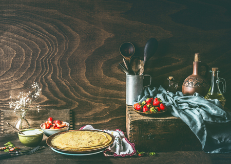 Country still life with homemade crepes on dark rustic wooden kitchen table with strawberries and yogurt in bowls .