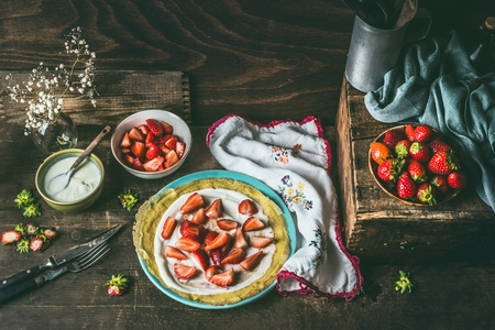 Homemade crepes on dark rustic kitchen table with strawberries and yogurt on blue plate . Country style food still life