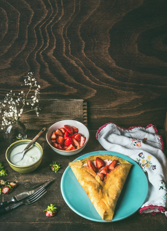 Homemade crepes on dark rustic kitchen table with strawberries and yogurt . Country style food still life