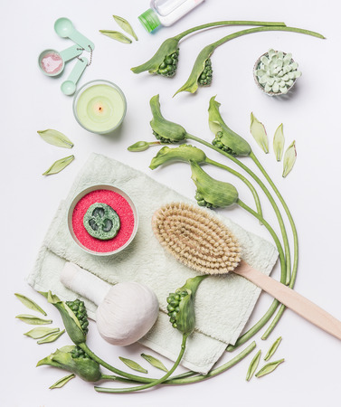 Various accessories and natural products for cellulite treatment at home on white background. Spa setting flat lay with tropical leaves and flowers. Massage tools. Beauty and body care concept