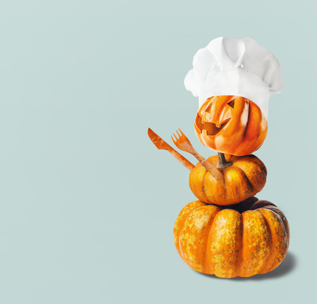 Funny Pumpkin Jack with chef hat and hands make with cutlery , with copy space. Halloween and Thanksgiving  cooking concept
