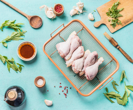 Raw chicken drumsticks for grill or roasting on roast grid with marinate, spice and seasoning on blue background, top view.