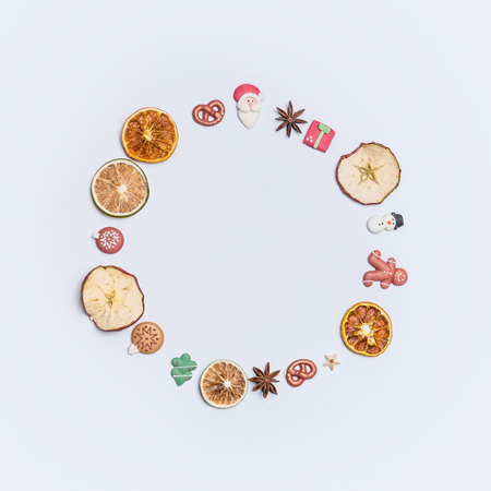Christmas round circle fame or wreath made with dried fruits and anise stars and marzipan Christmas decor figures: Santa, tree, ginger man, snowman and balls on white background, top view, flat lay