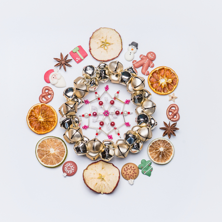 Christmas round circle frame or wreath made with dried fruits and anise stars and marzipan Christmas decor , bells and snowflake on white background, top view, flat lay Stockfoto