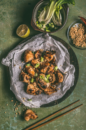 Close up of fried teriyaki chicken pieces with peanut and spring onions on table background with chopsticks and ingredients. Asian food concept Stock Photo