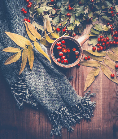 Autumn concept. Scarf and cup of tea decorated with fall leaves on dark rustic wooden table background , top view, still life Stok Fotoğraf