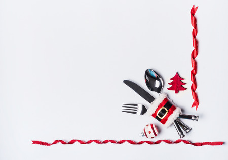 Christmas dinner table setting with cutlery decorated with Santa's belt, Christmas tree and ribbons on white background, top view with copy space. Flat lay Standard-Bild
