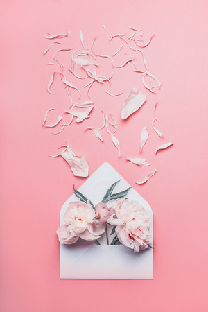 White envelope with peonies and scattered petals of flowers on pastel pink background, top view with copy space for your design 免版税图像