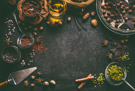 Dark chocolate background for confectionery or patisserie with broken crushed chocolate pieces , cocoa powder , nuts, cocoa beans, spices, spirits and vintage kitchen utensils, top view, frame Stock Photo