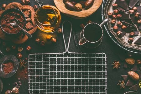 Dark chocolate background for confectionery or patisserie with broken chunks crushed chocolate pieces , cocoa powder , nuts, cocoa beans, spices, spirits and vintage kitchen utensils, top view Stock Photo - 110956213