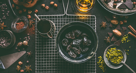 Soaked in rum prunes for homemade pralines with various chocolate and nuts ingredients on dark table background with vintage kitchen utensils, top view. Confectionery or patisserie concept