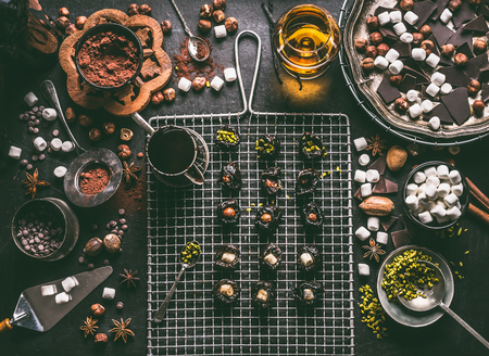 Confectionery or patisserie concept. Preparation of pralines with prunes soaked in rum and stuffed with nuts, marshmallow and pistachio on dark table background with chocolate and ingredients