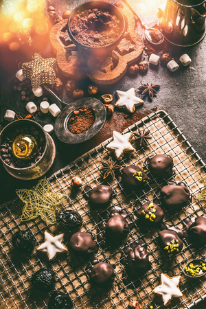 Homemade chocolate praline on dark rustic table with cacao powder , nuts, marshmallows and cinnamon star Christmas cookies. Home holidays cuisine and sweet gifts making. Christmas food Stock Photo - 110956218