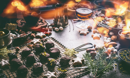 Homemade chocolate praline on dark table with nuts, marshmallows and cinnamon star Christmas cookies. Home holidays cuisine and sweet gifts making. Christmas food. Cozy festive homely atmosphere Stock Photo