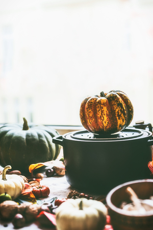 Black cast iron cooking pot with pumpkins on kitchen table background with ingredients at window. Autumn cooking and eating concept. Fall still life