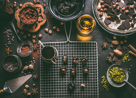 Homemade chocolate pralines preparation on dark rustic table background with vintage kitchen utensils and ingredients. Prunes stuffed with nuts and melting chocolate, top view Stockfoto