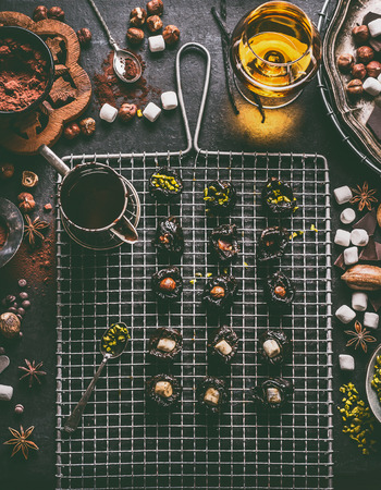Homemade chocolate pralines preparation on dark rustic table background with vintage kitchen utensils and ingredients. Prunes filled with nuts, pistachios and marshmallow. Top view Stock Photo - 111555652