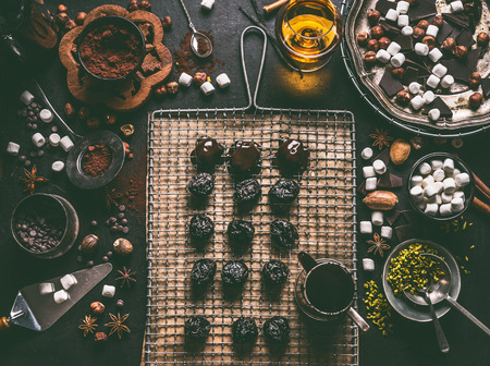 Homemade pralines preparation on dark rustic table background with vintage kitchen utensils. Stuffed prunes with nuts, pistachios and marshmallow and covered with melting chocolate. Top view