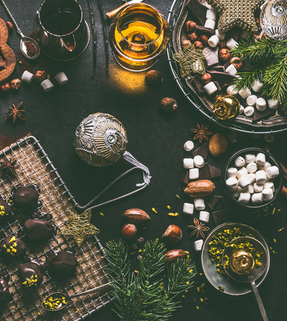 Christmas food background with chocolate, marshmallow, cookies, homemade pralines , cacao , nuts and spirits on dark rustic table with vintage kitchen utensils and ingredients, top view
