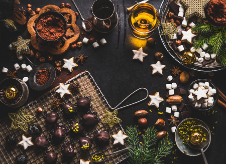Christmas sweet background with chocolate, marshmallow, cookies, homemade pralines , cacao , nuts and spirits on dark rustic tables with vintage kitchen utensils and ingredients, top view