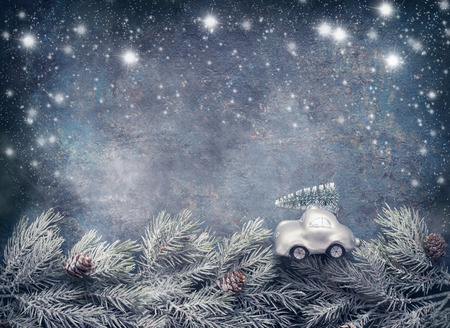 Christmas tree on toy car rides on fir branches on dar blue background with painted snow. Greeting card with copy space for your design Imagens