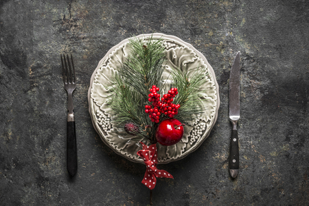 Festive Christmas table setting for holiday dinner with plate, cutlery, fir branches , red apple and winter berries on rustic background, top view