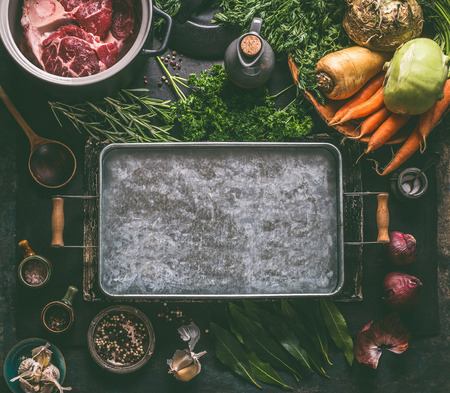 Food background. Ingredients for tasty Ham Hock Soup : raw beef meat shin with bone, root vegetables, herbs and spices around tray on dark rustic kitchen table with cooking spoon and cast iron pot Reklamní fotografie - 111555700