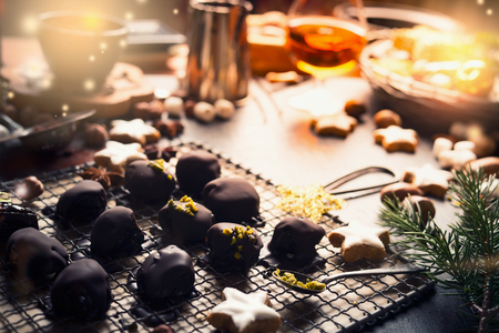 Homemade festive confectionery , pralines and truffles on dark rustic background with ingredients. Christmas sweets patisserie background with cozy candle light Stockfoto