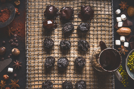 Homemade pralines and truffles on dark kitchen table background with melting chocolate and ingredients, top view
