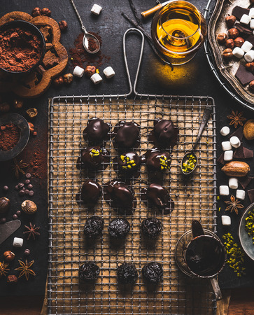 Homemade patisserie. Handmade pralines and truffles making preparation on dark table background with ingredients: brocken chocolate, various nuts, spices, cacao powder and spirits, top view