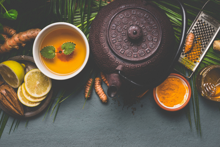 Teapot and healthy turmeric spice tea with lemon,  ginger and honey on dark background , top view.  Immune boosting remedy , detox and dieting concept