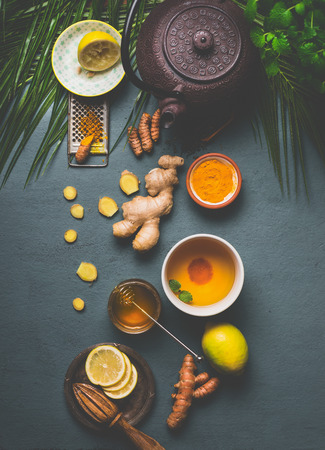 Ingredients for healthy turmeric spice tea on gray background with teapot, cup of tea,  lemon,  ginger, cinnamon sticks and honey , top view.  Immune boosting remedy , detox and dieting concept