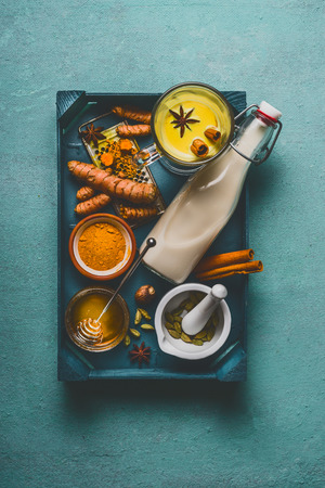 Healthy golden turmeric milk on tray with ingredients: cardamom, turmeric, cinnamon, honey and ginger on blue background , top view, vertical.  Immune boosting remedy , detox and dieting concept. Stock Photo