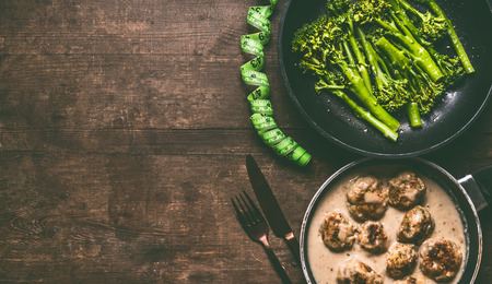 Low carb dieting meal with meat balls, blanched broccoli in cooking pan, cutlery and measure tape on wooden table background, top view with copy space. Healthy weight loss diet food concept