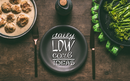 Plate with cutlery and text lettering: Daily low carb ideas on wooden background with meat balls, broccoli and  measure tape, top view. Healthy weight loss diet food concept