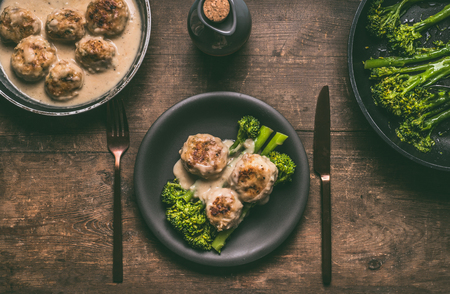 Plate with cutlery and low carb dieting meal: meat balls and blanched broccoli on wooden table background, top view with copy space. Healthy weight loss diet food Stock Photo