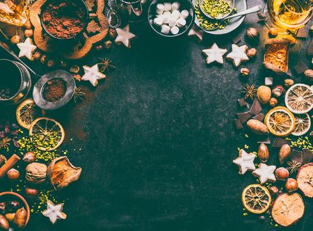 Weihnachtsgewürze, Schokolade und Kekse Hintergrund mit Zutaten zum Backen und süßen Speisen: Nüsse, Trockenfrüchte, gebrochene Schokolade und Spirituosen auf dunklem Hintergrund, Draufsicht mit Kopienraum für Design Standard-Bild