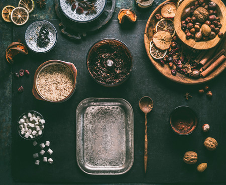 Preparation of homemade vegan chocolate truffle pralines with dried fruits and nuts mix, ingredients on dark background, top view. Healthy sweets. Energy vegan balls with dates, cocoa and almond Stock Photo