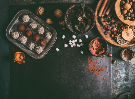 Homemade vegan chocolate truffle pralines with dried fruits and nuts mix ingredients on dark background, top view, border. Healthy sweets. Energy vegan balls with marshmallow Stock Photo - 112801551