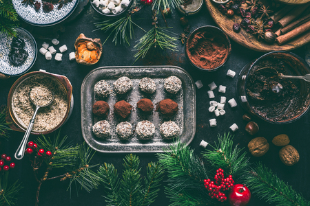 Homemade vegan chocolate truffle pralines for Christmas with dried fruits and nuts mix ingredients on dark background, top view, border. Healthy sweets. Energy vegan balls with dates, cocoa and almond Stock Photo - 112801552