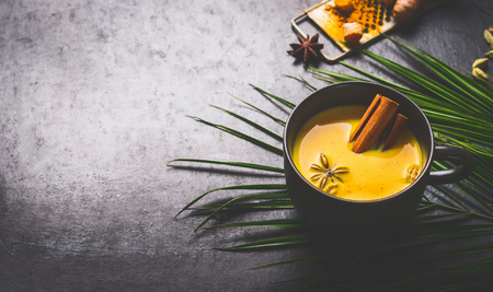 Golden turmeric milk text with spices, honey on dark background with ingredients and palm leaves. Healthy hot drink. Immune boosting remedy , detox and dieting concept