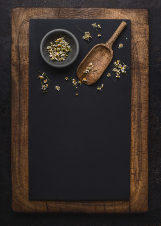 Dark chalkboard background with dried chamomile flowers and wooden shovel spoon , top view with copy space for your design. Healing herbs and herbal medicine concept. Vertical