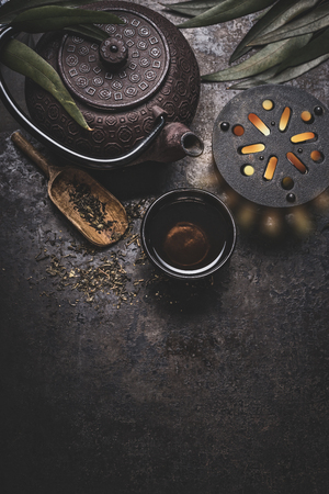 Black iron asian tea set on dark rustic background with teapot and fresh tea leaves, top view with copy space for your design. Authentic vintage style Standard-Bild - 112801696