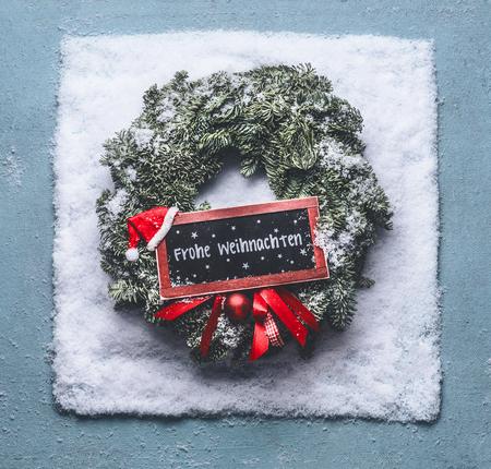 Frohe Weihnachten-Text in deutscher Sprache. Weihnachtskranz mit grünen Tannenzweigen und rotem gerahmtem Schild und Weihnachtsmütze im Schnee auf blauem Hintergrund, Draufsicht mit Tafelkopierraum für Ihren Text oder Design.