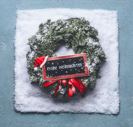 Frohe Weihnachten text in german. Christmas wreath with green fir branches and red framed sign and Santa hat in snow on blue background, top view with chalkboard copy space for your text or design. Stock Photo