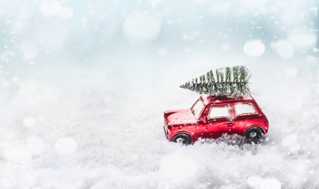 Christmas tree on roof of red retro car toy in snow through snowy winter wonderland with snowfall. Creative Christmas holiday concept. Copy space for your greeting and design. Front view