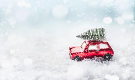 Weihnachtsbaum auf dem Dach des roten Retro-Autospielzeugs im Schnee durch verschneites Winterwunderland mit Schneefall. Kreatives Weihnachtsferienkonzept. Kopieren Sie Platz für Ihre Begrüßung und Ihr Design. Vorderansicht