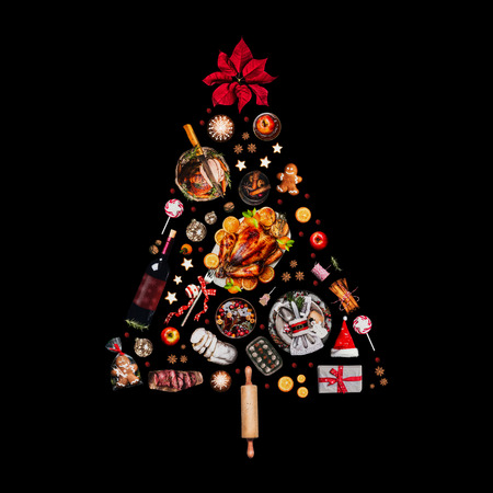 Christmas tree made with various Christmas food: turkey on platter, roasted ham, sweets and candies, cookies , mulled wine, gingerbread  man decorated with gift box and poinsettia. Isolated on black Stock Photo